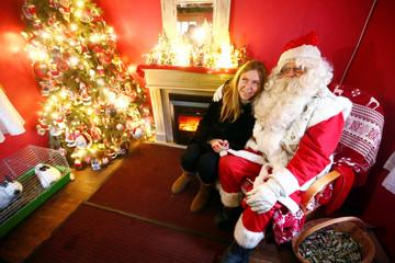 A woman sits next to a man dressed as Santa Claus in Tallinn