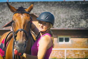 Rider woman talking to her horse. Portrait of riding horse with woman in helmet. Stable in background.