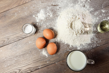 Top view of the egg, flour, a glass of fresh milk, cooking dough on the background of a wooden table. Flat lay, copy space.
