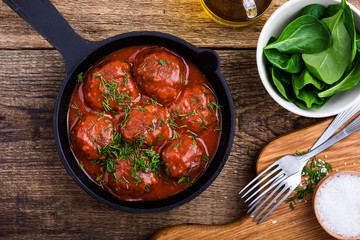 Beef meatballs in cast iron skillet on rustic wooden table