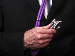 Man wearing a suit holding a stethoscope