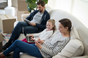 Parents and daughter using electronic devices