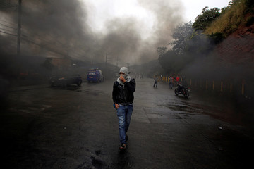 An opposition supporter walks amid smoke during clashes with police in Tegucigalpa