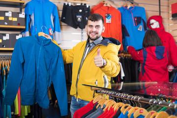Couple choosing jacket in store