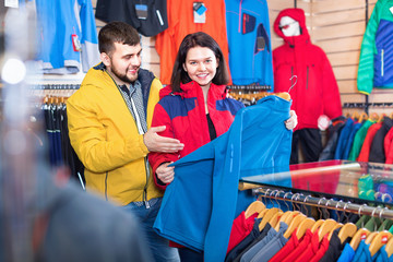 Couple examining track jackets in sports clothes store