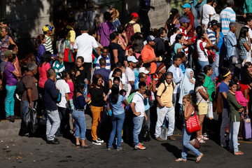 People try to find other modes of transportation after subway services were halted during a massive blackout in Caracas