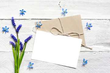 blank white greeting card and envelope with spring blue flowers bouquet and buds