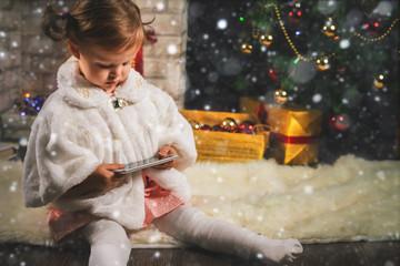 little girl making selfie on mobile phone at Christmas