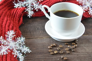 cup of coffee with grains, red burgundy scarf, wooden, winter concept, hot drink, snowflakes on dark background
