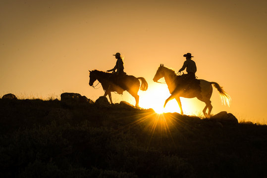 Silhouetted western cowboy and cowgirl on horseback against yellow sunset