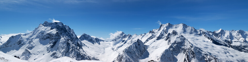 Fototapete - Panoramic view of snow-capped mountain peaks