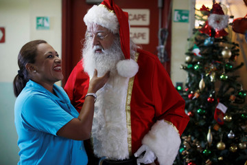 Icelander Einar Sveinsson, dressed as Santa Claus, poses for a picture with a nurse during a visit to the Benjamin Bloom National Children Hospital in San Salvador