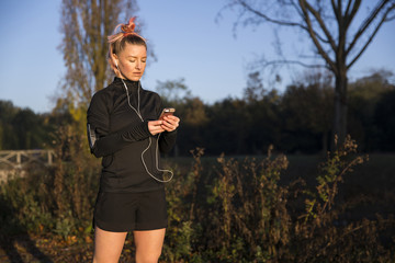 Woman using smart phone while exercising at park