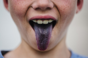 Midsection of boy sticking out purple tongue