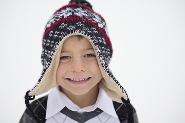 Close-up portrait of smiling boy wearing knit hat during winter