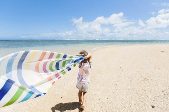 Boy holding blanket on beach