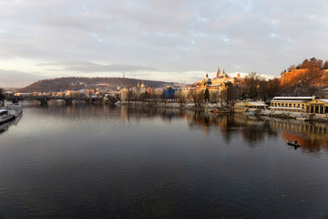Early Morning Christmas snowy Prague Lesser Town with gothic Castle above River Vltava, Czech republic