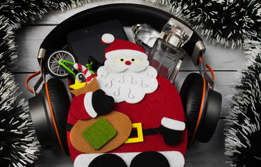 Santa bag with headphones, smartphone, toy bicycle diamond & perfume bottle laying on a white wooden table with christmas decoration.