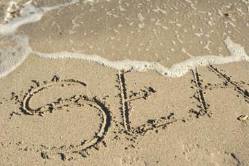 sea written in a sandy tropical beach