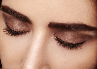 Perfect shape of eyebrows, brown eyeshadows and long eyelashes. Closeup macro shot of fashion smoky eyes visage