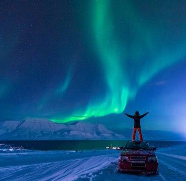 The polar arctic Northern lights aurora borealis sky star in Norway Svalbard man in Longyearbyen city the moon mountains