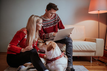 Christmas gifts and happiness between a young couple and a cute dog