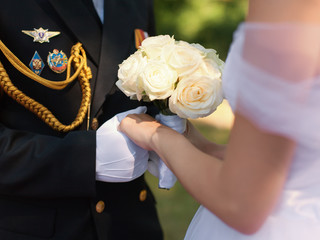 Hands of officer in gloves and bride with wedding bouquet