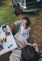 Back view of woman taking photo to happy young friend while having a breakfast in campsite