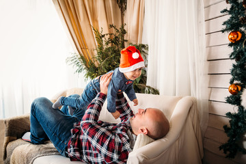 Christmas family portrait of happy smiling father playing with small kid in red santa hat. Winter holiday Xmas and New Year concept