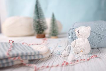 White toy bear sits near woolen light blue ball of yarn