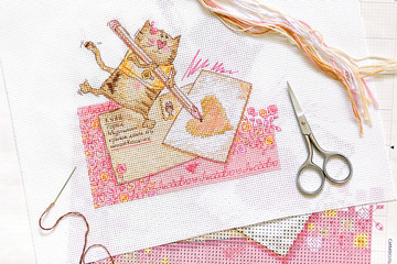 Cross-stitch set : embroidery with cat pattern , scissors, canvas and colorful yarn. View from above. Freelance, hobby, handmade home decor concept.