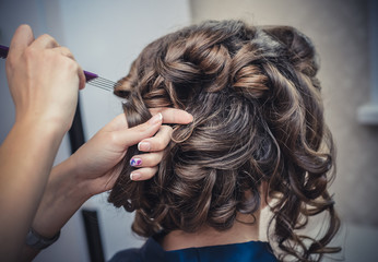 The hands of the hairdresser do wedding hairstyle