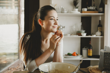 Dreaming smiling woman while cooking
