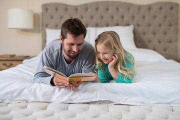 Father and daughter reading a book while lying on bed