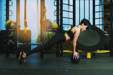 Young woman doing plank exercise on blue ball