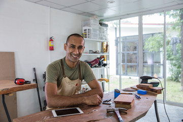Portrait of a smiling carpenter in his studio