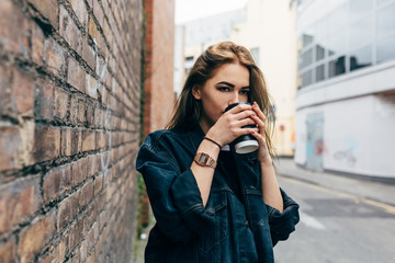 Young Beaufitul Woman Holding a Coffee To Go