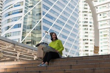 Happy female tourist with suitcase exploring map while sitting in city building, Travel concept