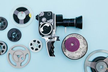 Vintage cinema camera and reels over pastel blue background