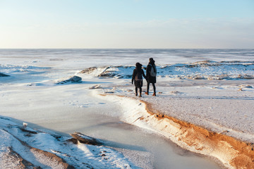 Young couple in love are traveling with backpacks  in snow desert