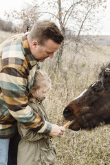 Father and daughter feeding horse