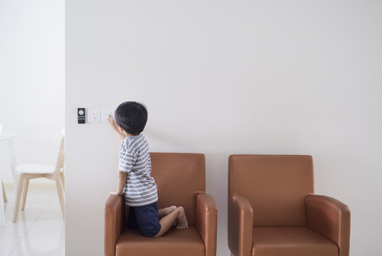 Little boy turning on/off switch