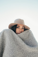 Black and white shot of a teen woman covered with a blanket