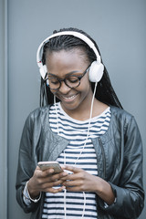 Female in headphones using smartphone