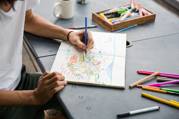 Young artist drawing in his notebook
