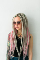 dreadlocked young woman on the white wall background