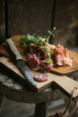 Cut salami and ham laying on wooden table