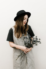 young woman with tattoos holding thistle flowers in front of white wall