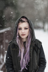 Portrait of a beautiful young woman with pink hair on snow
