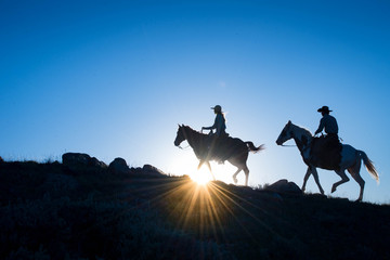 Silhouetted cowboy and cowgirl on horseback, with a blue sky and setting sun at horiozn